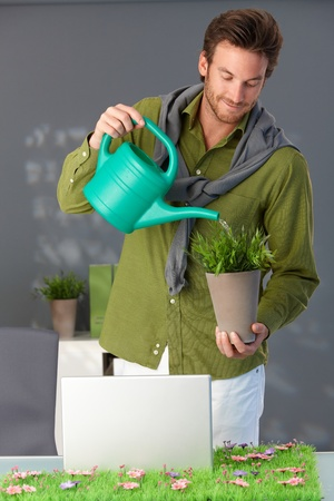 potted plant: Handsome smart man watering plant at home, standing at spring field table with flowers and laptop computer.
