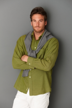 Goodlooking man standing with arms folded, looking at camera, grey background. Stock Photo - 10373416