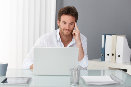 home office desk: Businessman working at office, sitting at desk, looking at laptop computer screen, smiling, thinking.