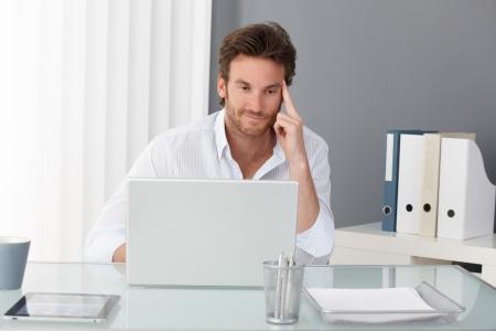 spokojený: Obchodník pracující v kanceláři, seděl u stolu, díval se na obrazovce přenosného počítače, s úsměvem, a přemýšlel.