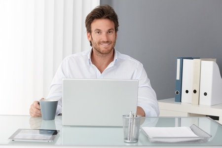 Happy businessman sitting in office, working with laptop computer, having tea, smiling at camera. photo