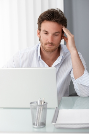 Businessman concentrating on computer work, using laptop, thinking, looking at screen, sitting at desk. photo