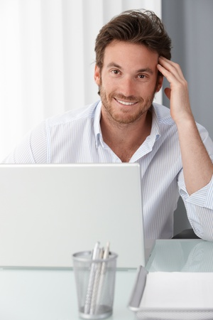 Happy businessman at office desk, using laptop computer, smiling at camera. photo