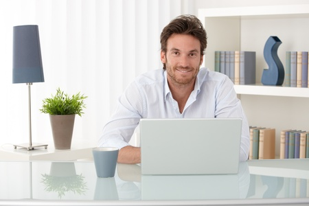 man working: Portrait of goodlooking man sitting at table at home with laptop computer, smiling at camera.