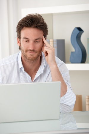 Smiling man using laptop computer at home, sitting at table in living room, looking at screen. Stock Photo - 10373349