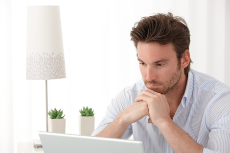offish: Portrait of thinking man using laptop computer at home, copyspace.