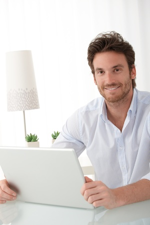 Portrait of happy man sitting at home with laptop computer, smiling at camera. Stock Photo