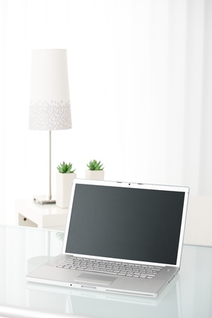 Laptop computer with screen visible on table in bright room, still-life picture.