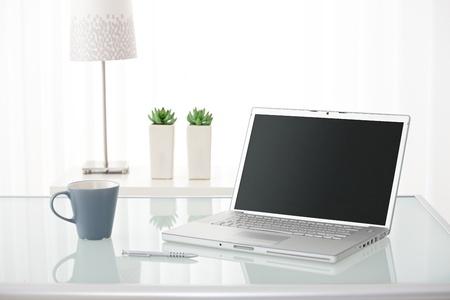 컴퓨터, 펜, 테이블, 램프 및 밝은 환경에서 식물에 커피 잔의 아직도 인생 초상화.