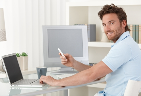 Man sitting at desk using laptop computer and phone at home, smiling at camera. Blank space on screens for your logo or image.