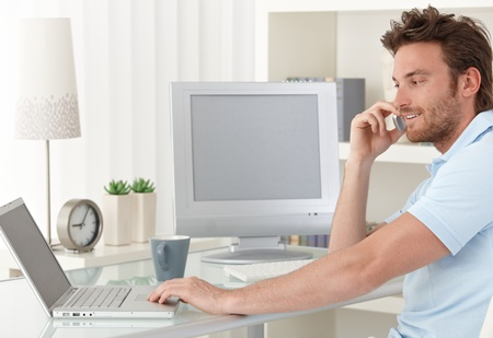 telecommuting: Smiling man talking on mobile phone while using laptop computer at desk in study. Blank space on screens for your logo or image. Stock Photo