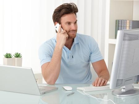 llamando: Oficina trabajador guy mostrador mediante ordenador port�til y m�vil en el trabajo, sonriendo, mirando la pantalla. Foto de archivo