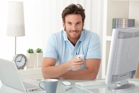 Smiling man at desk with mobile phone handheld, looking at camera, having computer.