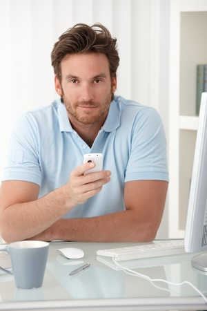 handheld: Portrait of smiling man sitting at desk with cellphone handheld, looking at camera.