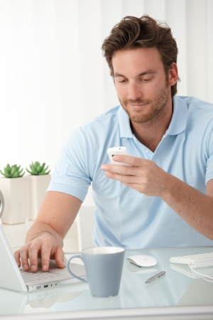 Smiling man using mobile phone for texting, typing on laptop computer, sitting at desk. photo