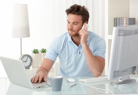 iş adamı: Casual businessman working at office desk, using mobile phone and laptop computer, typing, making phone call, smiling.