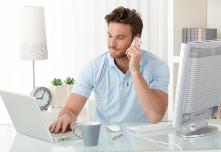 persona llamando: Empresario casual en mesa de oficina, utilizando el teléfono móvil y el ordenador portátil, escribiendo, haciendo llamadas, sonriendo.