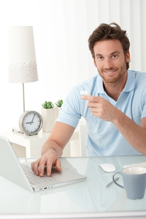 Smiling office worker guy sitting at desk with mobile phone handheld, typing on laptop computer, looking at camera. Stock Photo - 10373315