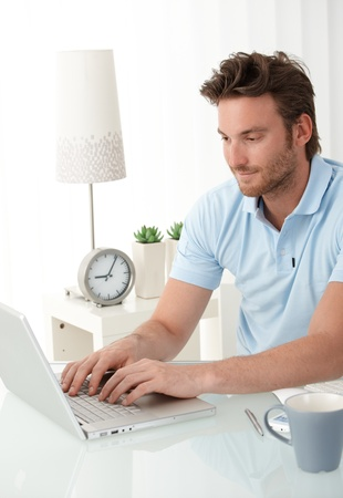 Handsome man typing on laptop computer keyboard, looking at screen, smiling.