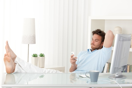 Man sitting relaxing at desk, bare feet on table, texting on mobile phone. Stock Photo - 10373309