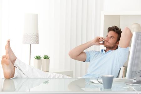 llamando: Relajado hombre sentado con los pies en alto sobre la mesa en casa, hablando por teléfono móvil, sonriendo.