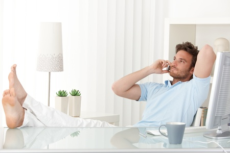 effortless: Relaxed man sitting with feet up on desk at home, talking on mobile phone, smiling. Stock Photo
