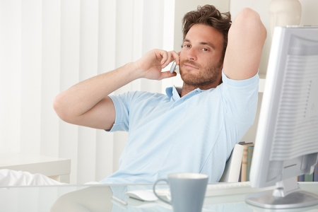 Portrait of handsome relaxed man sitting at desk making phone call on mobile, smiling. photo