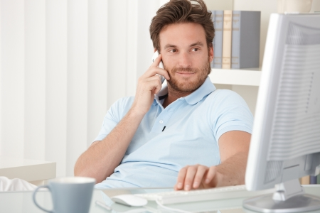 handheld computer: Portrait of smiling man speaking on mobile phone, sitting at desk, looking at computer screen.