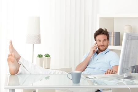 pies masculinos: Enfriar el hombre con los pies hasta el escritorio haciendo llamadas de teléfono móvil, escribiendo en el teclado, sonriendo, mirando la pantalla del ordenador.