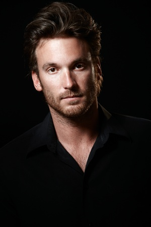 only 1 man: Portrait of handsome man wearing black shirt, black background, looking at camera. Stock Photo