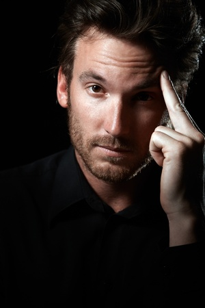Closeup portrait of handsome man in black thinking, looking at camera. photo
