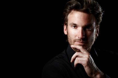 visage homme: Closeup portrait de la pensée homme confiant, vêtu de noir, en regardant la caméra, fond noir.