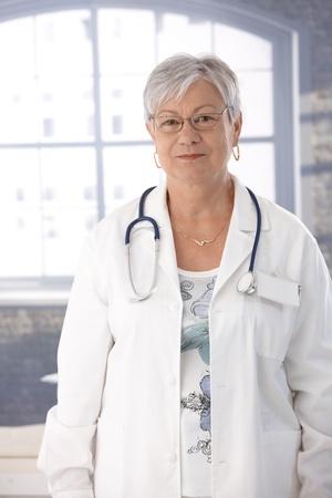 lab coat: Anziano medico femminile in piedi davanti alla finestra in camice da laboratorio. Archivio Fotografico
