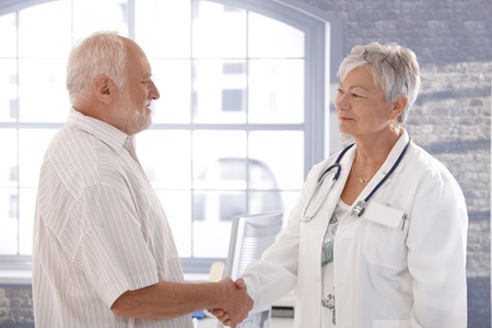 Senior female doctor and male patient shaking hands, smiling.