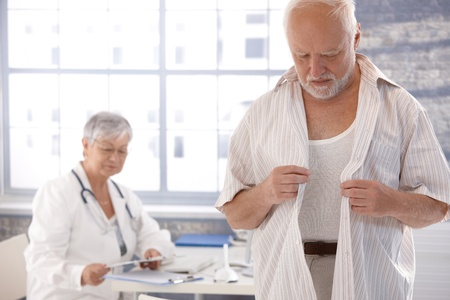 undressing woman: Mature male patient undressing at doctors room. Stock Photo