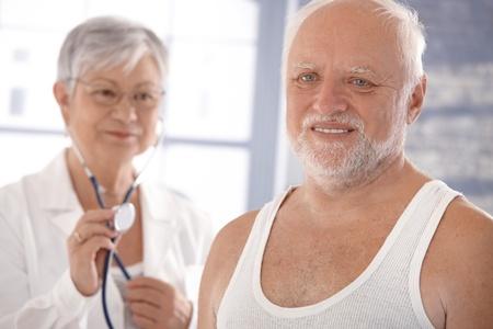 undershirt: Senior man on health control in doctors room. Stock Photo