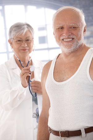Smiling old man waiting for examination, senior doctor with stethoscope in the background. photo