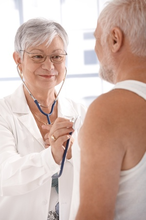 Smiling female doctor examining mature man. photo
