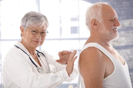 Elderly man examined by senior female doctor. photo