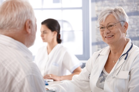 explanations: Senior doctor consulting with old man at her office.
