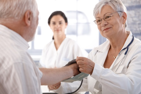 consultant physicians: Senior female doctor measuring old mans blood pressure. Stock Photo