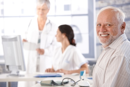 Elderly man waiting for examination at doctor's room, smiling. Stock Photo - 10373345