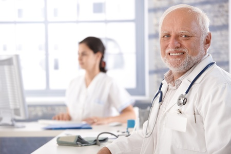 Senior doctor sitting at desk in office, smiling, looking at camera. photo