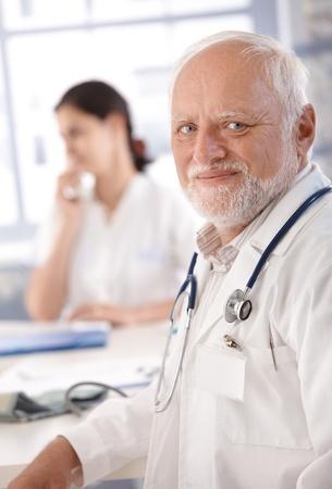 Portrait of senior doctor smiling at doctors room. photo