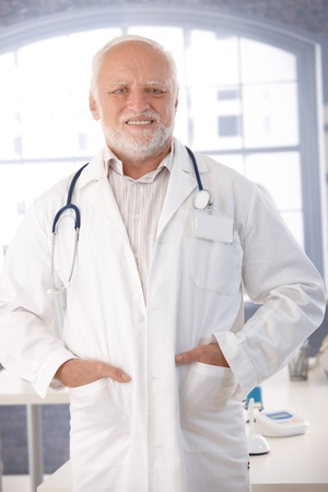 Mature doctor smiling in lab coat in his room. photo