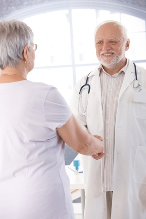 consultant physicians: Senior doctor and female patient shaking hands.
