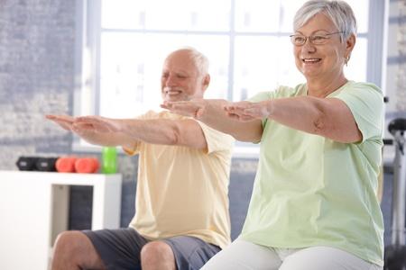 mujeres sentadas: Personas maduras ejercer alegremente en el gimnasio.