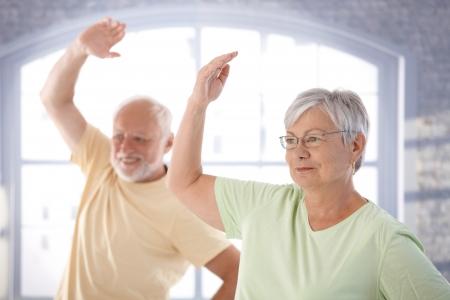 mujeres mayores: Pareja de ancianos haciendo ejercicios en el gimnasio. Foto de archivo