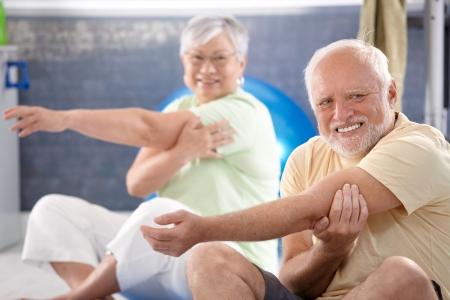 hombres haciendo ejercicio: Senior personas haciendo ejercicios de estiramientos en el gimnasio. Foto de archivo