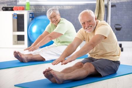 растягивание: Пожилая пара растяжения в тренажерном зале.